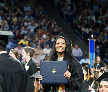 a new graduate holds her diploma at commencement