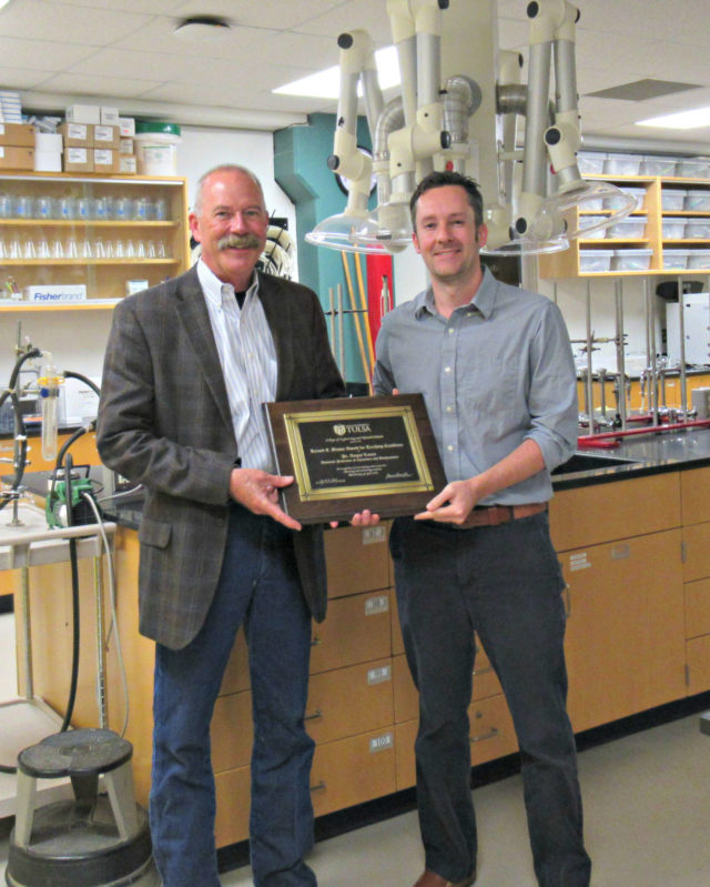 two men standing in a chemistry lab holding an award plaque