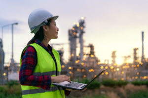 young woman wearing a hard hat and a high-visibility vest holding a laptop and standing in front of an oil refinery