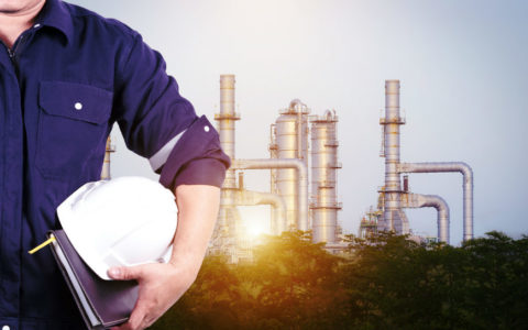 partial view of a man holding a white hardhat in front of an oil refinery with the sun shining through it