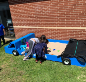 two little children playing in a sandbox designed to look like a car